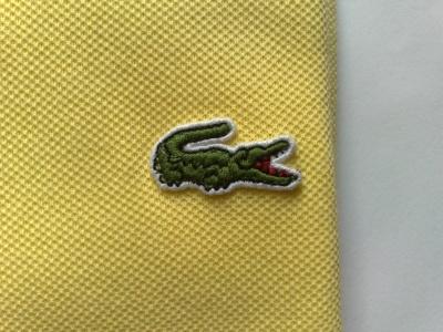 логотип на поло Lacoste. На поло Lacoste логотип пришивается тонкой леской. В некоторых коллекциях логотип может выглядеть иначе: быть большего размера или другого цвета.